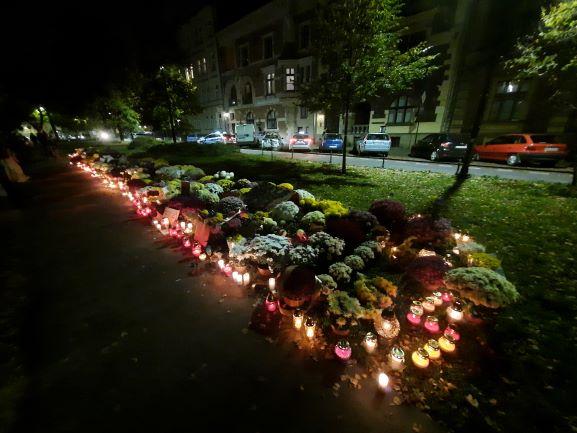 Dywan z kwiatów i zniczy pod siedzibą PiS w Krakowie